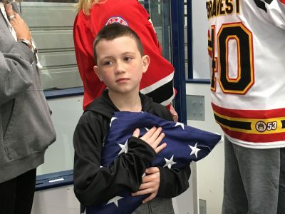Johnny holds Ray's flag during National Anthem.