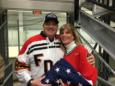 Joe and Marion Pfeifer holding onto Ray's flag.
